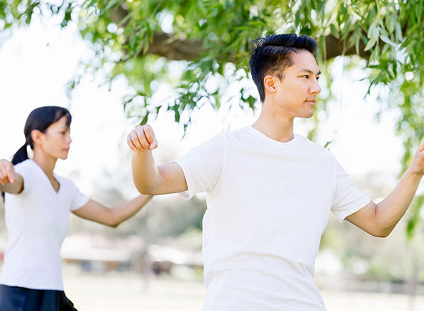 two people doing tai chi in a serene park